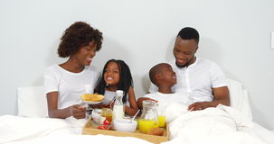 Happy family having breakfast together on bed stock footage