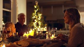 Happy family having Christmas dinner. Happy family celebrating christmas together at home. Family sitting at dining table talking and having dinner together on stock video footage