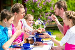 Family having coffee time in garden eating cake Royalty Free Stock Photos