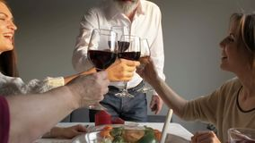 Happy family having dinner party, drinking red wine and toasting at home stock video footage