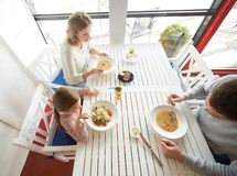Happy family having dinner at restaurant or cafe Royalty Free Stock Images