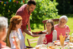 Happy family having dinner or summer garden party. Leisure, holidays and people concept - happy family having festive dinner or summer garden party Stock Image