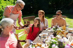 Happy family having dinner or summer garden party. Leisure, holidays and people concept - happy family having festive dinner or summer garden party Stock Images