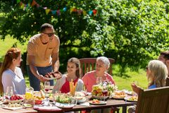 Happy family having dinner or summer garden party Stock Images