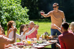 Happy family having dinner or summer garden party. Leisure, holidays and people concept - happy family having festive dinner or summer garden party and Royalty Free Stock Photography