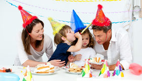 Happy family having fn while eating birthday cake. In the kitchen stock photo