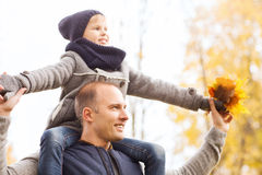 Happy family having fun in autumn park Stock Photos
