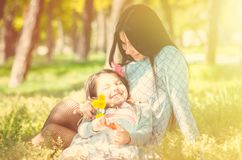 Happy family having fun. baby girl with curly hair and his mother smiles each other. outdoor shot.  Stock Photography