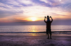 Happy family having fun on the beach. Father and son play on the Beach in sunrise silhouette shot Stock Photography