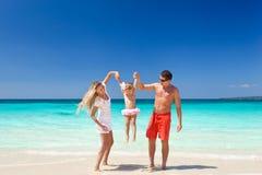 Happy family having fun on beach Stock Photos