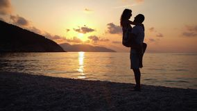 Happy family having a fun at beach at sunset over the sea. Slow molion footage stock video