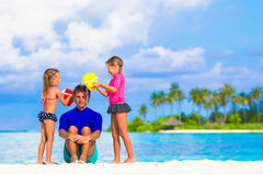 Happy family having fun on beach vacation. Father and two girls playing with sand on tropical beach Stock Image