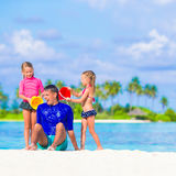 Happy family having fun on beach vacation. Father and two girls playing with sand on tropical beach Stock Photography