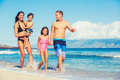 Happy Family Having Fun at the Beach. Young Happy Family Having Fun at the Beach Outdoors Royalty Free Stock Photography