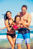 Happy Family Having Fun at the Beach. Young Happy Family Having Fun at the Beach Outdoors Royalty Free Stock Photo