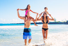 Happy Family Having Fun at the Beach. Young Happy Family Having Playing Fun at the Beach Outdoors Stock Photo
