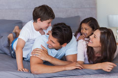 Happy family having fun on the bed Royalty Free Stock Images