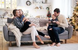 Happy family having fun in bedroom. Cheerful young family with kids sitting on sofa royalty free stock images