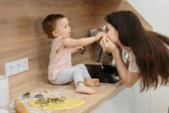 Mother and child daughter preparing the dough, bake cookies. Happy family having fun on the kitchen. mother and child daughter preparing the dough, bake cookies royalty free stock photography