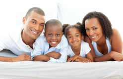 Happy family having fun lying down on bed Stock Image