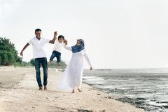 Happy family having fun at muddy beach located in pantai remis royalty free stock photography