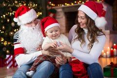 Happy family having a fun near Christmas tree and. Happy family with child son having a fun near Christmas tree and fireplace  in living room Stock Image