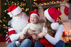 Happy family having a fun near Christmas tree and. Happy family with child son having a fun near Christmas tree and fireplace  in living room Royalty Free Stock Image