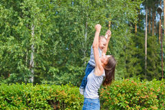 Happy family having fun outdoors. Mother holding son in the air like airplane royalty free stock photography