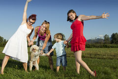 Happy family having fun outdoors on a sunny day, w. Ith cute dog Stock Images