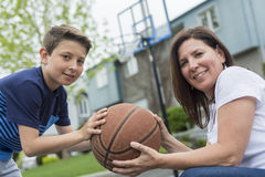 Happy family having fun outside with a basketball. royalty free stock images