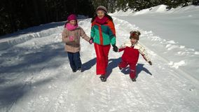 Happy family having fun playing in a snowy forest in the mountains in winter. Mom and her two children. They happily run. Through the snow to the camera. HD stock footage
