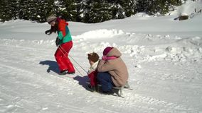 Happy family having fun playing in a snowy forest in the mountains in winter. Mom and her two children are sledding. They are laughing. HD stock video