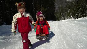 Happy family having fun playing in a snowy forest in the mountains in winter. Mom and her two children are sledding. They are laughing. HD stock footage