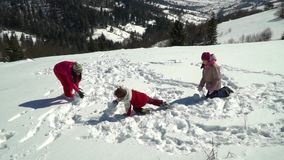 Happy family having fun playing in a snowy forest in the mountains in winter. Mom and her two children throw snowballs. They are laughing. Slow motion stock video footage