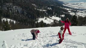 Happy family having fun playing in a snowy forest in the mountains in winter. Mom and her two children throw snowballs. They are laughing. Slow motion stock footage