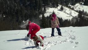 Happy family having fun playing in a snowy forest in the mountains in winter. Mom and her two children throw snowballs. They are laughing. Slow motion stock video