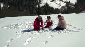 Happy family having fun playing in a snowy forest in the mountains in winter. Mom and her two children throw snowballs. Making a snowman. They are laughing stock video