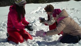 Happy family having fun playing in a snowy forest in the mountains in winter. Mom and her two children throw snowballs. Making a snowman. They are laughing stock footage