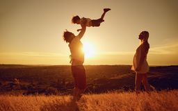 Happy family having fun playing at sunset on nature. royalty free stock image