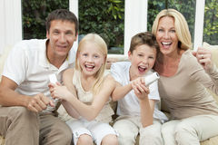 Happy Family Having Fun Playing Video Games. Happy family, parents, son and daughter, having fun playing video console together, the children have the remote Stock Photo