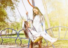 Happy family having fun ride on a swing . baby girl with curly hair and his mother smiles each other. outdoor shot.  Stock Photo