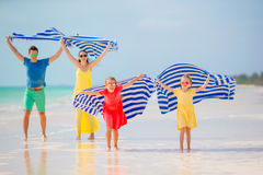 Happy family having fun running with towel and enjoying vacation on tropical beach with white sand and turquoise ocean Stock Photos
