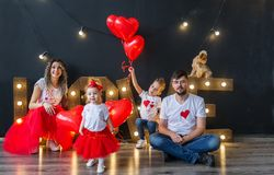 Happy family having fun on saint valentine`s day. Parents with little kids with heart baloons royalty free stock images