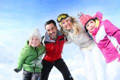 Happy family having fun in snowy mountains Stock Photos
