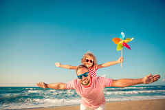 Happy family having fun on summer vacation. Happy family on the beach. People having fun on summer vacation. Father and child against blue sea and sky background Stock Photography