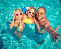 Happy family having fun on summer vacation. Father, mother and child playing in swimming pool. Active healthy lifestyle concept Stock Image
