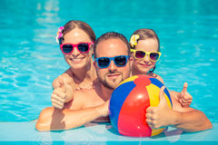 Happy family having fun on summer vacation. Father, mother and child playing in swimming pool. Active healthy lifestyle concept Royalty Free Stock Photos