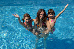 Happy family having fun in swimming pool. On summer vacation, mother and kids Royalty Free Stock Photos