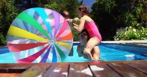 Happy family having fun in swimming pool stock video