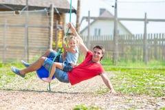 Happy family having fun on a swing outdoors Stock Photos